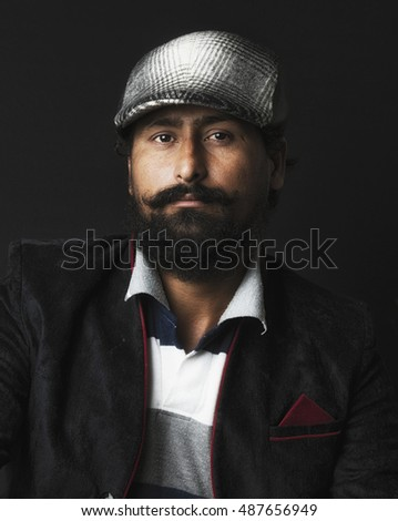 Artistic portrait of Indian Smart Young bearded man on black background