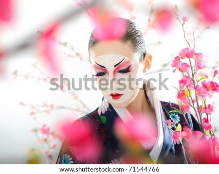 Artistic portrait of japan geisha woman with creative make-up near sakura tree - stock photo