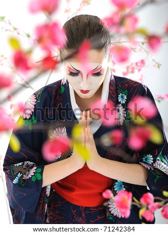 Artistic portrait of japan geisha woman with creative make-up near sakura tree in kimono - stock photo