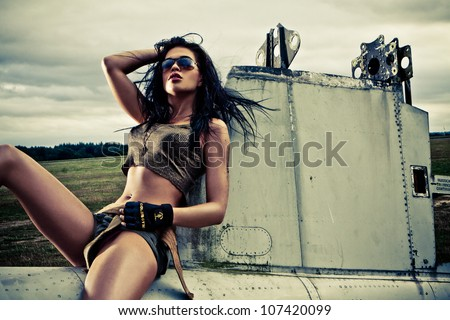 Artistic portrait of sexy slender long-legged woman in skimpy two piece outfit sitting on the fuselage of an abandoned old plane on a stortmy day - stock photo