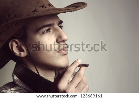 Artistic portrait of the young beautiful man. The young man smokes a cigar