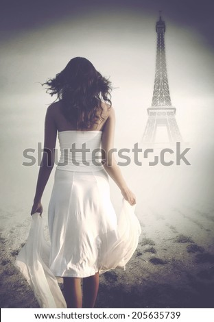Artistic rear view of a brunette mysterious woman wearing white long skirt, top and holding a veil while walking towards the Eiffel Tower, in a misty atmosphere, in Paris, France - stock photo