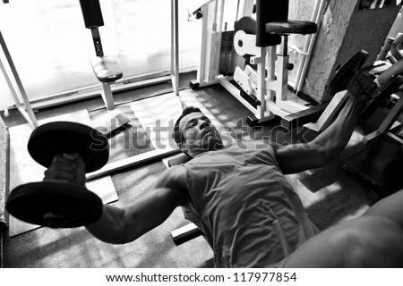 artistic shot, black and white, of a young bodybuilder hard training in the gym: incline dumbbell press
