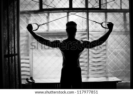 artistic shot, black and white, of a young bodybuilder hard training in the gym: shoulders - rear cable crossover