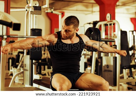 artistic shot, golden retouch, of a young bodybuilder hard training in the gym: tensing muscles on the bench press