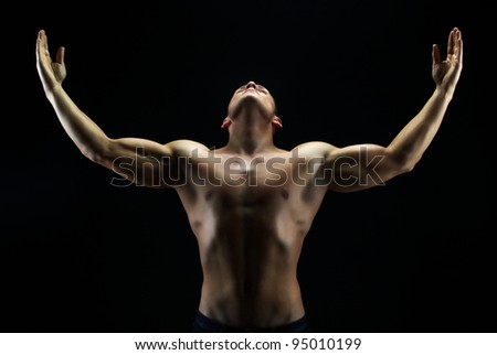 Artistic shot of a guy with his hands up against black background - stock photo