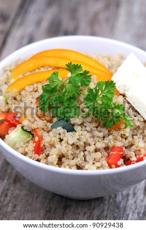 Artistic shot of quinoa salad on rustic wooden background - stock photo