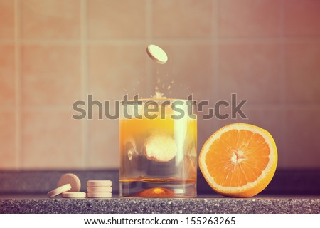 Artistic shot of vitamin C family, orange, tablet stack, dissolving tablet  - stock photo