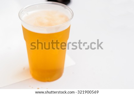 Artistic soft focus plastic glass of beer on a white table with copy space for text