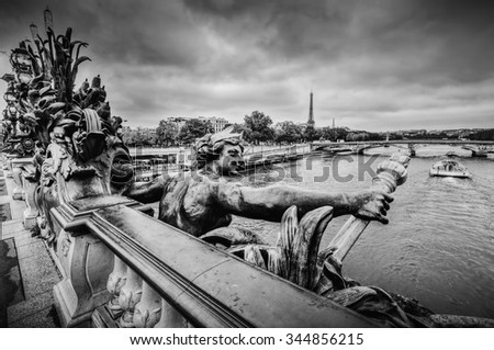 Artistic statue on Pont Alexandre III bridge in Paris, France. Seine river and Eiffel Tower. Black and white - stock photo