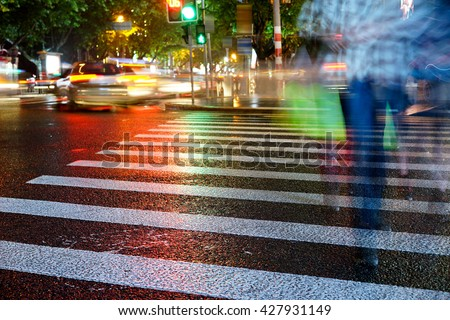 Artistic style - Night view of Crosswalk and pedestrian at modern city zebra crossing street in rainy day. Blur abstract.Background concept. - stock photo