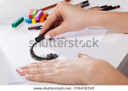 Artistic tools and woman painted black pastel - stock photo