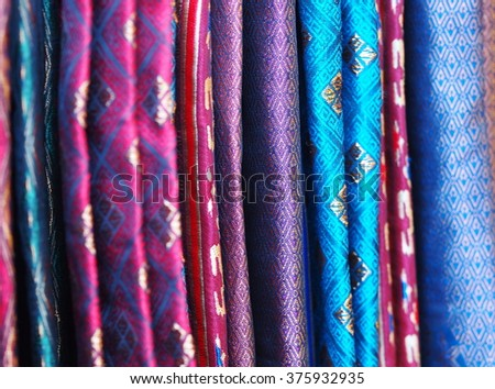 artistic variety shade tone colors ornaments patterns of thai silk textiles with traditional cultural decoration ornaments crafts by village people hanging in a street market in KHONKAEN, THAILAND  - stock photo