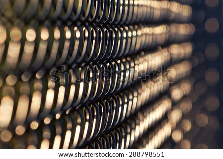 Artistic view of black chain link fence in early evening sunlight. Horizontal background. fence chain links are in focus near center, fade to abstract, out of focus shapes left and right.