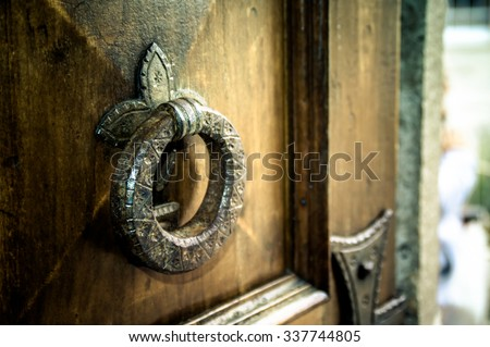 Artistic vintage dark edit of an old iron metal door knocker on an open wooden door, background with copy space for text - stock photo