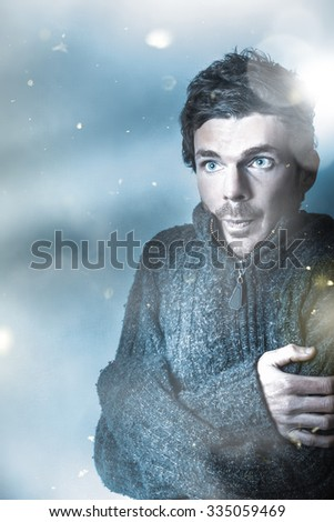 Artistic winter fashion portrait of a cold young man freezing in the blue frost of falling snow.  In season clothes - stock photo