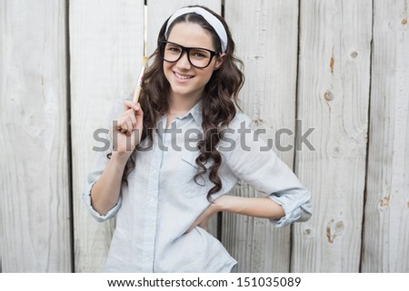 Artistic woman with stylish glasses posing holding paintbrush on wooden background - stock photo