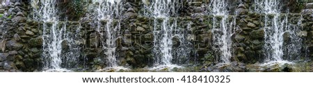 Artistic work of my own.  Intentional blur. Panorama waterfall, cascade flowing over mossy boulders in a botanical garden. - stock photo
