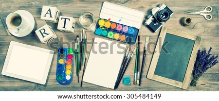 Artistic workplace mockup. Watercolor, brushes, digital tablet pc, chalkboard, vintage no name camera, office supplies and tolls. Retro style toned picture - stock photo
