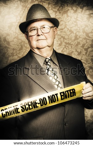 Artistically aged portrait of an astute fifties crime investigator with a stoical expression watching carefully for any clues or odd behaviour as he unwinds the yellow tape at a fresh crime scene - stock photo