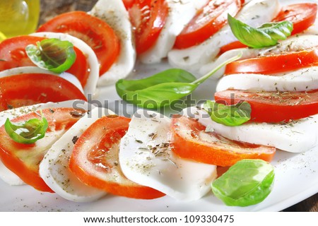 Artistically arranged cheese and tomato salad in alternating slices of red and white garnished with fresh herbs - stock photo