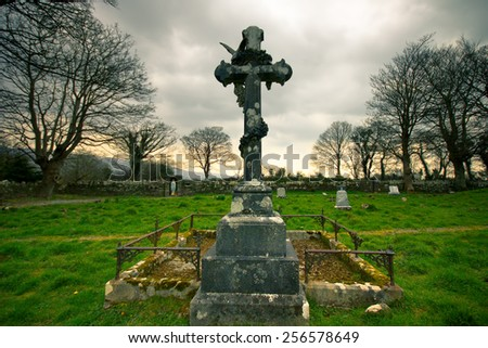 Artistically toned image of Crucifix gravemarker at abandoned Castlehyde church and cemetery in Cork Ireland - stock photo