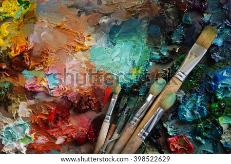 artists brushes and oil paints on wooden palette. Vintage stylized photo of paintbrushes closeup and artist palette. palette with paintbrush and palette-knife - stock photo