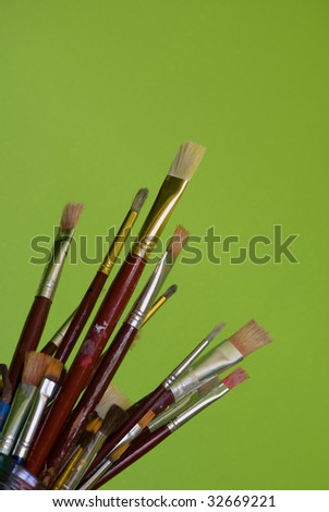 Artists brushes on green - stock photo