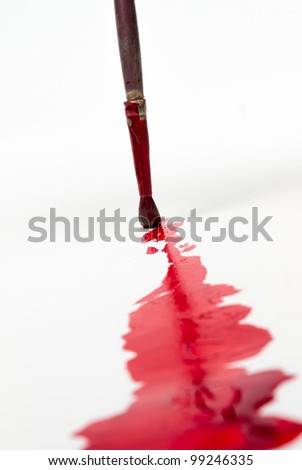 Artists paint brush and paint red on white canvas. - stock photo