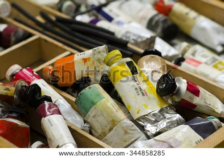 Artists paint tubes; used tubes of oil paints in work box; differential focus  - stock photo