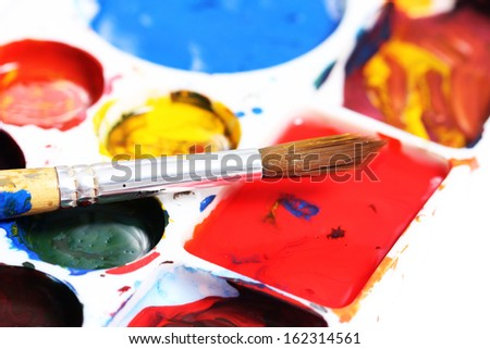 artists palette loaded with various colour paints and brush - stock photo