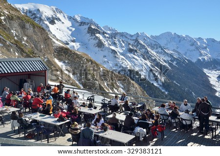 ARTOUSTE, PYRENEES, FRANCE - JANUARY 01, 2015: Skiers rest in the outdoor terrace of alpine ski resort upper the mountain valley d'Ossau, ARTOUSTE, PYRENEES, FRANCE - JANUARY 01, 2015. - stock photo
