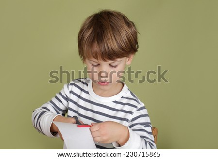 Arts and crafts activity, child learning to cut with scissors, learning and education concept