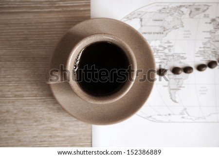 artwork  in grunge style,  cup of coffee, coffee beans and political map of the world - stock photo