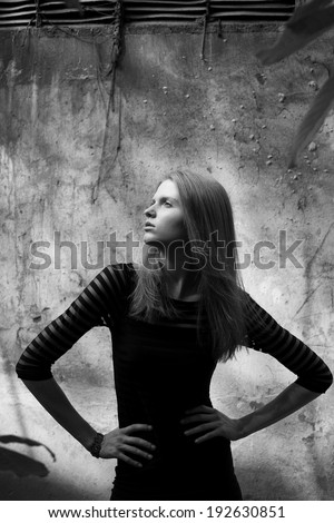 Arty portrait of a beautiful model in black striped cocktail dress with jabot of tree's leaves posing over old stone wall with metal constructions. Urban (vogue) style. Black and white outdoor shot - stock photo