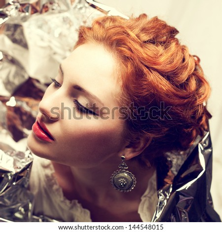 Arty portrait of a fashionable queen-like red-haired (ginger) model with silver foil cape posing over white curtain background. Vintage (classic, retro) style. Close up. Studio shot - stock photo