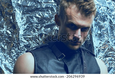 Arty portrait of young handsome blue-eyed man with trendy haircut with strong intense look in sleeveless zip-front vest of dark jeans posing over silver foil background. Close-up. Studio shot - stock photo