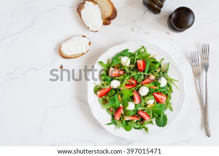 Arugula, baby spinach, strawberries and mozzarella cheese salad. Healthy green salad for dieting, snack or light dinner. Table top view food on white plate on white background - stock photo