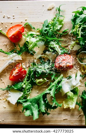 Arugula salad with tomatoes and parmesan, salad  of arugula, arugula and tomato, salad on a wooden board, salad on a brown background, salad with sesame seeds - stock photo