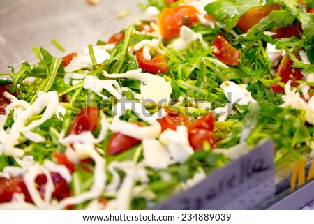 Arugula, tomato and mozzarella on focaccia bread on display at a snack bar - stock photo