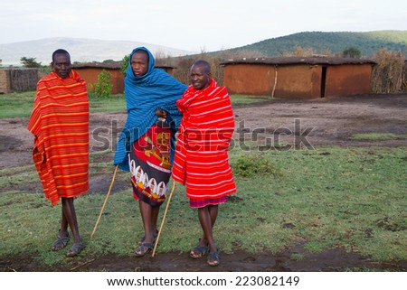 ARUSHA, TANZANIA - AUGUST 10: Masai men in a typical pose in their camp, masai people still live in the old way with traditional dress august 10, 2014 in Arusha, Tanzania - stock photo