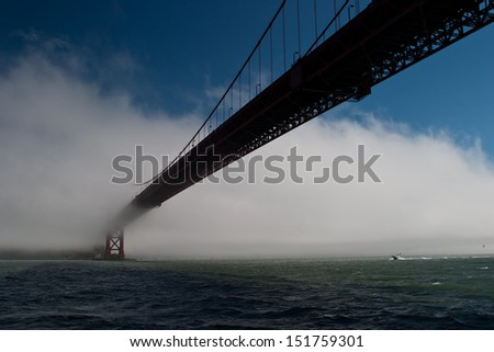 As fog drifts in from the Pacific Ocean to cover San Francisco the Golden Gate bridge slowly disappears.  The bridge is one of the city's most iconic sites.
