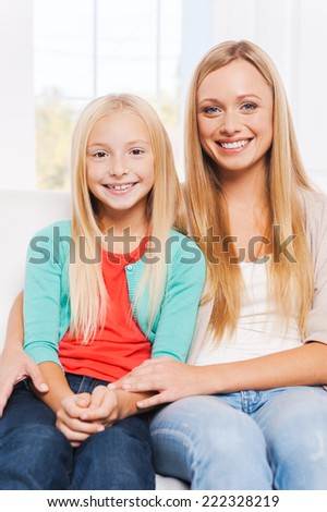 As mother as daughter. Happy mother and daughter bonding to each other and smiling while sitting on the couch together  - stock photo