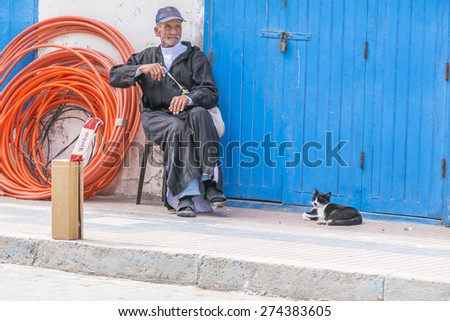 AS-SAWIRA, MOROCCO, APRIL 7, 2015: Elderly man sells cigarettes sitting in company of his cat - stock photo