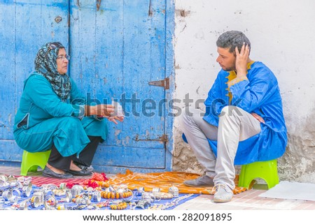AS-SAWIRA, MOROCCO, APRIL 7, 2015: street sellers of local jewelry chat waiting for buyers - stock photo