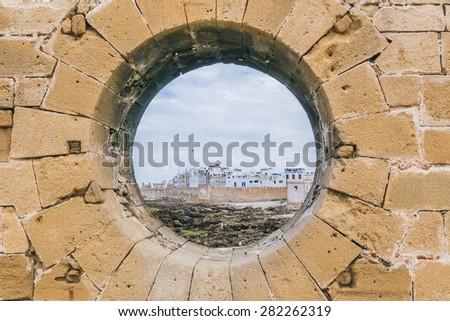 As-Sawira, Morocco - circular hole in historic ramparts with view on medina - stock photo
