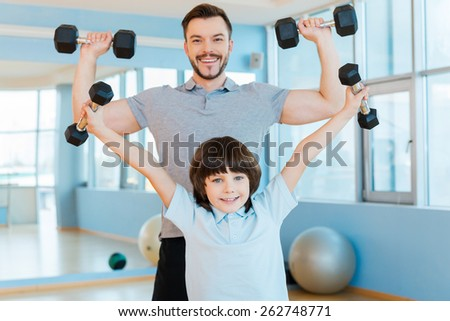 As strong as my father. Happy father and son exercising with dumbbells and looking at camera while both standing in health club