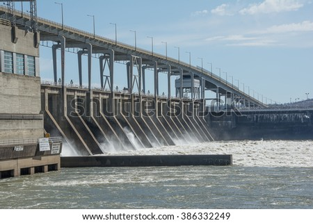 As the river's water flows across the hydroelectric generator rotors, electrical power is produced.The power is then conditioned at the power house. It is then routed by power poles to several states.
