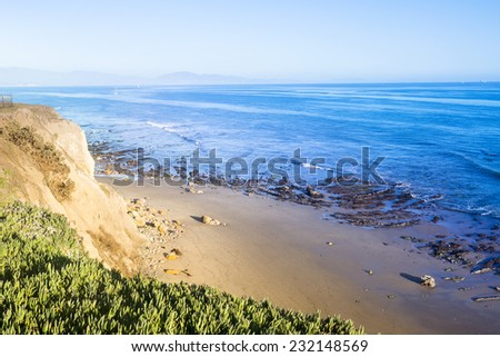 As the sun sets it lights up the side of a cliff in a rich, yellow tone as viewed from the edge of a cliff. - stock photo