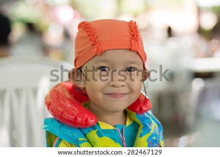 Asain kid in swimming pool. - stock photo